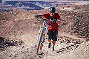 SHOT 10/15/16 4:29:48 PM - Doug Starkey of Steamboat Springs, Co. pushes his bike uphill during a climbing section along the White Rim Trail. The White Rim is a mountain biking trip in Canyonlands National Park just outside of Moab, Utah. The White Rim Road is a 71.2-mile-long unpaved four-wheel drive road that traverses the top of the White Rim Sandstone formation below the Island in the Sky mesa of Canyonlands National Park in southern Utah in the United States. The road was constructed in the 1950s by the Atomic Energy Commission to provide access for individual prospectors intent on mining uranium deposits for use in nuclear weapons production during the Cold War. Four-wheel drive vehicles and mountain bikes are the most common modes of transport though horseback riding and hiking are also permitted.<br /> (Photo by Marc Piscotty / © 2016)