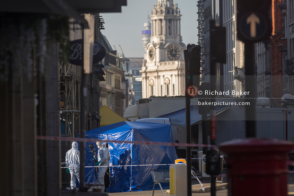 The morning after the terrorist attack at Fishmongers Hall on London Bridge, in which Usman Khan (a convicted, freed terrorist) killed 2 during a knife a attack, then subsequently tackled by passers-by and shot by armed police - forensic officers work on recording evidence outside one entrance to Monument Underground station, on 30th November 2019, in London, England.