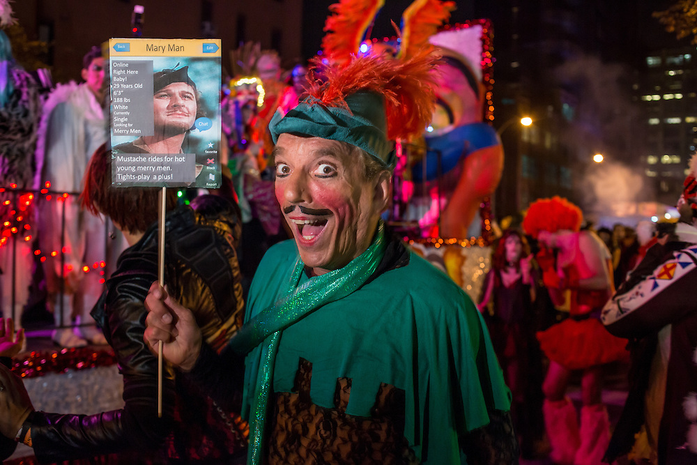 "New York, NY - 31 October 2015. A man in heavy makeup, wearing a green Robin Hood costume, carries a sign that says ""Mary Man"", and advertising that he's looking for merry men."
