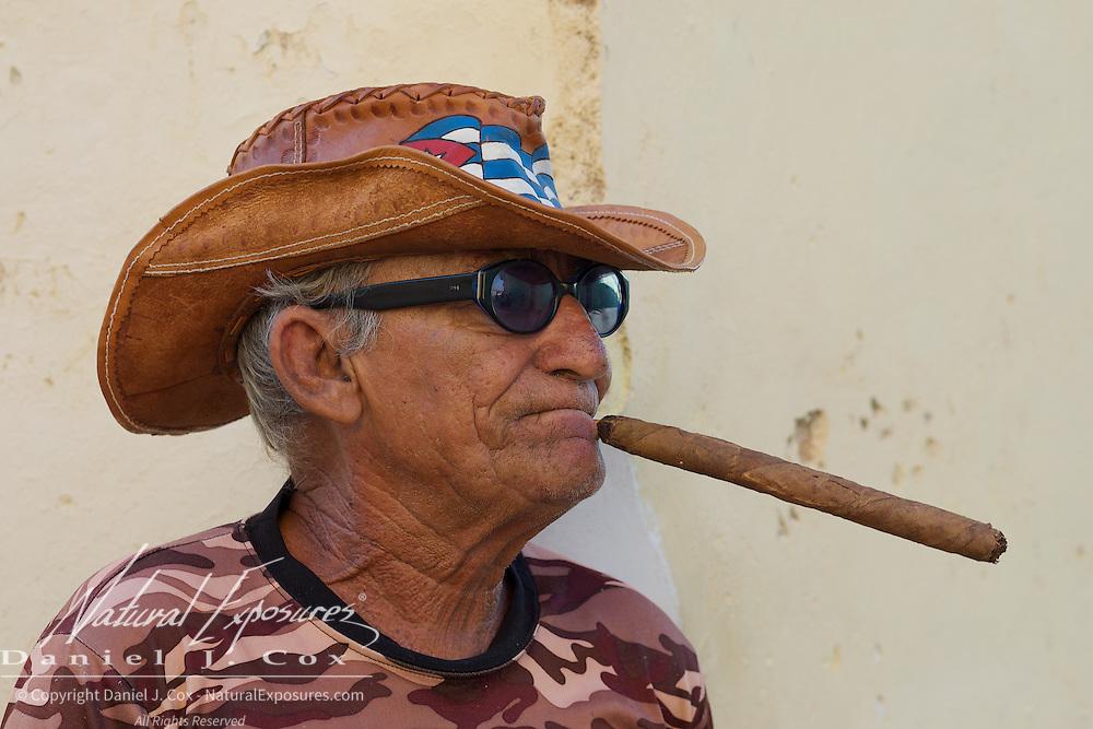 A Cuban man smoking a large Cuban cigar, Trinidad, Cuba.