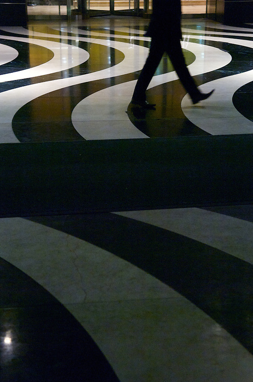 Curving patters in marble surround a pedestrian.