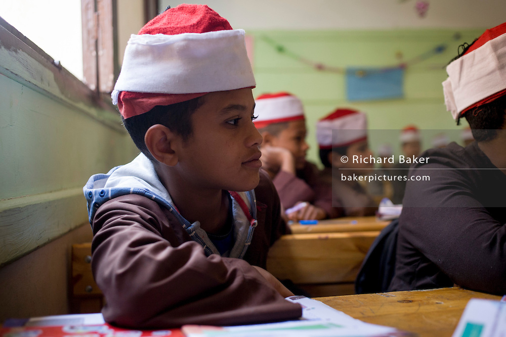 Schoolboys listen to their teacher in a classroom at the Islamic Koom al-Bourit Institute for Boys in the village of Qum (Koom), on the West Bank of Luxor, Nile Valley, Egypt.