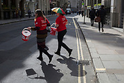 With their donation buckets swinging, two women charity fundraisers for the Red Cross cross Cornhill in the City of London, the capital's financial district, on 10th May 2019, in London, England.