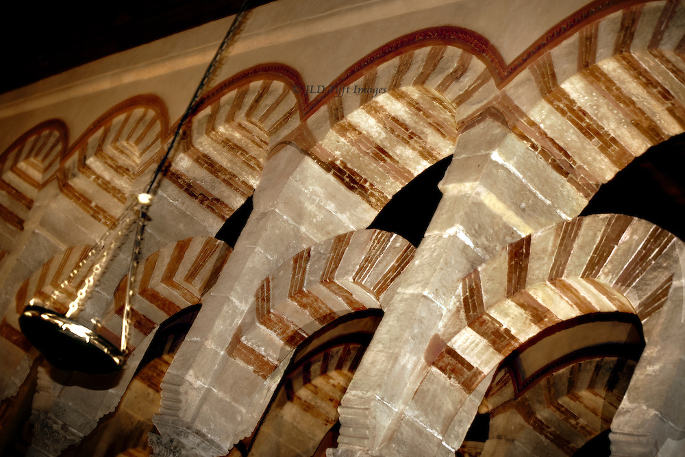Detail of the overlapping arches in the Grand Mosque of Cordoba, or Mezquita.  Image is tilted to create a diagonal patterns of the red brick stripes in the arches.  A hanging lamp illuminates them.