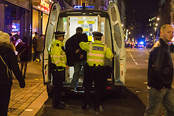 London, January 01 2018. Police put an arrested suspect into a van on Shaftesbury Avenue as revellers in London's West End enjoy New Year's Eve. © SWNS