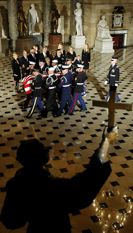The casket of former U.S. President Gerald R. Ford is carried by military pallbearers through Statutory Hall in the U.S. Capitol past Ford's family, including wife Betty, in Washington, DC on Saturday 30 December 2006. Ford will lie in state at the Capitol until Tuesday 02 January 2006, when a funeral will be held at the National Cathedral in Washington, D.C.