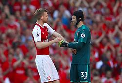 Arsenal goalkeeper Petr Cech gives the captains armband to Arsenal's Per Mertesacker