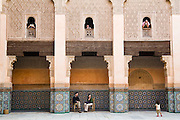 A man films his daughter from the windows giving in on the inner courtyard at the Ali ben Youssef Medersa in the Marrakech medina, Morocco on November 16, 2007.