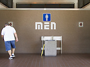 man going to the toilet at a rest stop facility USA.