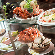 Examples of some of the dishes available from the restaurants in the center of the  Mercado Central de Santiago, Chile's central market. The market specializes in seafood, a staple food category of Chilean cuisine. The building is topped with an ornate cast-iron roof.