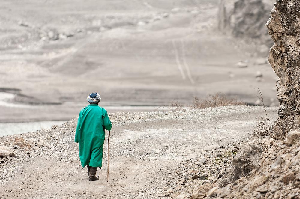 Stock photograph of an Old Tajik man in a green coat walking on a road away from the viewer in western Tajikistan