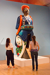 © Licensed to London News Pictures. 08/06/2014. London, UK. Two women looks at a ships figurehead from HMS Calcutta that stands four metres tall at the British Folk Art exhibition at Tate Britain in Millbank, London on 8th June 2014. The British Folk Art exhibition at Tate Britain opens on 10th June 2014 and runs until 31st August 2014. Photo credit : Vickie Flores/LNP