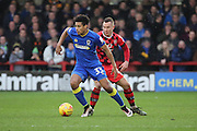 AFC Wimbledon striker Lyle Taylor (33) dribbling and holding off Walsall defender Matt Preston (16) during the EFL Sky Bet League 1 match between AFC Wimbledon and Walsall at the Cherry Red Records Stadium, Kingston, England on 25 February 2017. Photo by Matthew Redman.