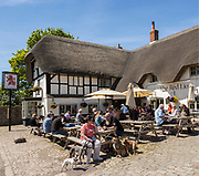 People drinking outside historic thatched Red Lion pub, Avebury, Wiltshire, England, UK