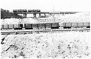 """Side view of three D&RG gondolas, #8215, #8899 and #8320, at Salida.  Two other gondolas, #8483 and an unidentified one, are on a trestle in the background with men either unloading their contents or cleaning the cars.<br /> D&RG  Salida, CO  Taken by Meigs, N. W. - ca. 1890<br /> In book """"Narrow Gauge Pictorial, Vol. III: Gondolas, Boxcars and Flatcars of the D&RGW"""" page 75"""
