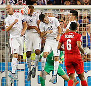 USA's Michael Bradley (4) John Brooks (6) and Ventura Alvarado (13) block a penalty kick by Panama midfielder Gabriel Gomez during the first half of a CONCACAF Gold Cup soccer match, Monday, July. 13, 2015, in Kansas City, Kan. (AP Photo/Colin E. Braley)