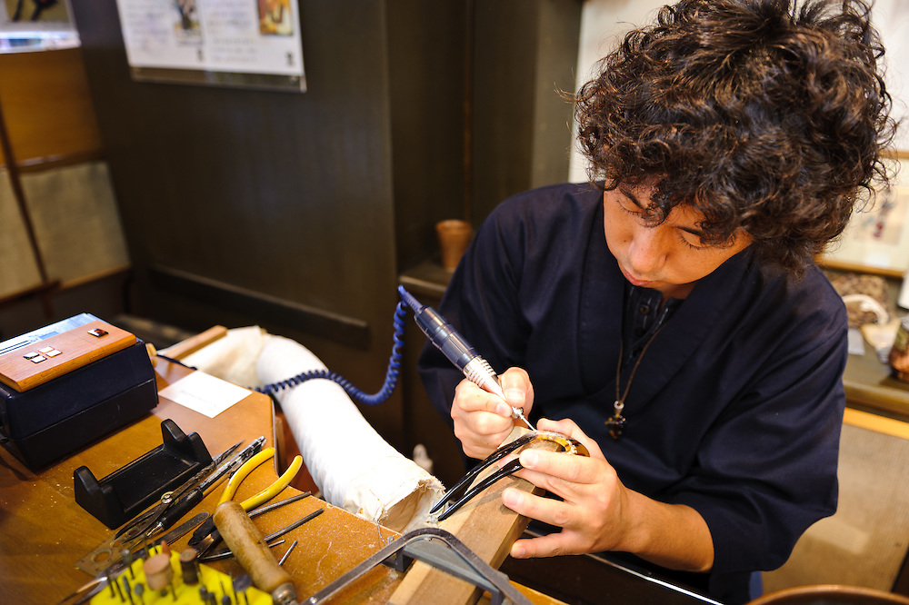 Artisan Tsuyoshi Isogai working on a tortoiseshell hairpin, Asakusa, Tokyo, Japan, August 28, 2011. Sensoji is one of the oldest temples in Tokyo, and the shopping arcades around it have sold visitors souvenirs for centuries.