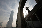 Workers on a construction site in Pudong Financial District with the Jinmao Grand Hyatt Tower in the back ground in Shanghai, China on 15 January 2010. Shanghai is on its way of becoming one of the world's most important financial centers.