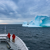 Guests on the bow of the National Geographic Explorer look at a spectacular pinnacled iceberg with an arch in Crystal Sound, Antarctica.