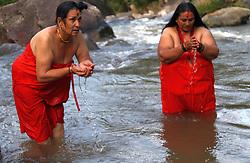 July 31, 2017 - Kathmandu, Nepal - Hindu women take holy bath and collect water from Bagmati river during the Bol Bom.pilgrimage at Sundarijal, Kathmandu.Devotees walk barefooted to Pashupatinath to offer the holy water. (Credit Image: © Archana Shrestha/Pacific Press via ZUMA Wire)