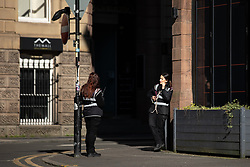 © Licensed to London News Pictures. 26/03/2020. Manchester, UK. Two traffic wardens talk on an empty street , stood two metres apart . Manchester City Centre lies nearly empty during a sunny spring afternoon . The British government has imposed a lockdown on all but essential activities and instructed people to reduce social contact as part of quarantine measures to prevent the spread of Coronavirus ( COVID-19 ) . Photo credit: Joel Goodman/LNP