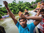 31 AUGUST 2014 - SARIKA, NAKHON NAYOK, THAILAND: Men bear small statues of Ganesh on their heads during the Ganesh Festival at Shri Utthayan Ganesha Temple in Nakhon Nayok. Ganesh Chaturthi, also known as Vinayaka Chaturthi, is a Hindu festival dedicated to Lord Ganesh. It is a 10-day festival marking the birthday of Ganesh, who is widely worshiped for his auspicious beginnings. Ganesh is the patron of arts and sciences, the deity of intellect and wisdom -- identified by his elephant head. The holiday is celebrated for 10 days, in 2014, most Hindu temples will submerge their Ganesh shrines and deities on September 7. Wat Utthaya Ganesh in Nakhon Nayok province, is a Buddhist temple that venerates Ganesh, who is popular with Thai Buddhists. The temple draws both Buddhists and Hindus and celebrates the Ganesh holiday a week ahead of most other places.    PHOTO BY JACK KURTZ