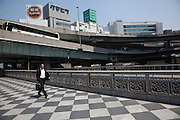 A Japanese salaryman walks on a bridge near the ramps and spans of the expressway overpass that snakes trough the city. Nihonbashi, Tokyo, Japan. Friday April 25th 2014