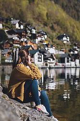 THEMENBILD - eine Frau sitzt am Ufer des Hallstätter Sees mit dem Panorama der Marktgemeinde an einem sonnigen Tag, aufgenommen am 17. April 2019 in Hallstatt, Österreich // a woman sitting on the shore of the Hallstatt lake with the panorama of the village on a sunny day during the Corona Pandemic in Hallstatt, Austria on 2020/04/17. EXPA Pictures © 2020, PhotoCredit: EXPA/ JFK
