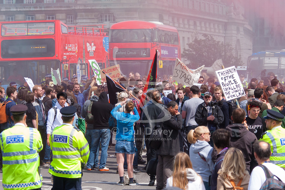 ter, London, May 30th 2015. Anti-austerity campaigners bring traffic on Westminster Bridge as they paint and hang a banner off the bridge highlighting an alleged £120 billion owed in taxes as compared to the proposed £12 billion cuts to welfare. PICTURED: Smoke from smokebombs billows across Westminster Bridge as the policeallow protesters to express themselves.