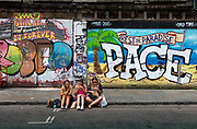 Young women sitting on the pavemnt eating lunch in front of street paintings on 2nd June 2017 in Brick Lane, London, United Kingdom. Set in the heart of the citys Bangladeshi-Sylheti community. It is famous for its many curry houses and more recently the area has also broadened to being a vibrant art and a fashionable area.