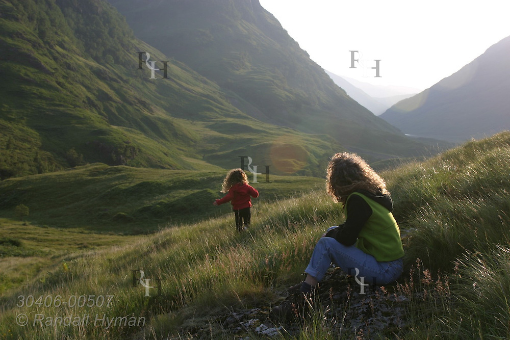 Mother watches daughter run away in grassy field of upper Glen Coe on a July afternoon; Glencoe Scotland.