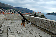 Child (9 years old) doing cartwheels on top tower of Fortress Lovrinjenac (Fort of Saint Lawrence), with Dubrovnik old town in background. Dubrovnik, Croatia