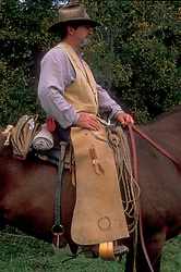 profile of a man in western clothes sitting on his horse