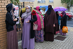 © Licensed to London News Pictures. 13/05/2021. London, UK. Muslim women wearing face coverings queue outside London Islamic Cultural Society and Mosque, also known as Wightman Road Mosque in north London for Eid al-Fitr prayers. Eid al-Fitr or the 'Festival of Breaking the Fast' celebrates the end of the month-long fast of Ramadan, and is being celebrated differently this year as a result of the coronavirus (COVID-19) pandemic. Prime Minister Boris Johnson announced that Covid-19 restrictions on social gatherings, meeting indoors and social contact will ease on May 17, meaning Eid celebrations this week still face restrictions.  Photo credit: Dinendra Haria/LNP