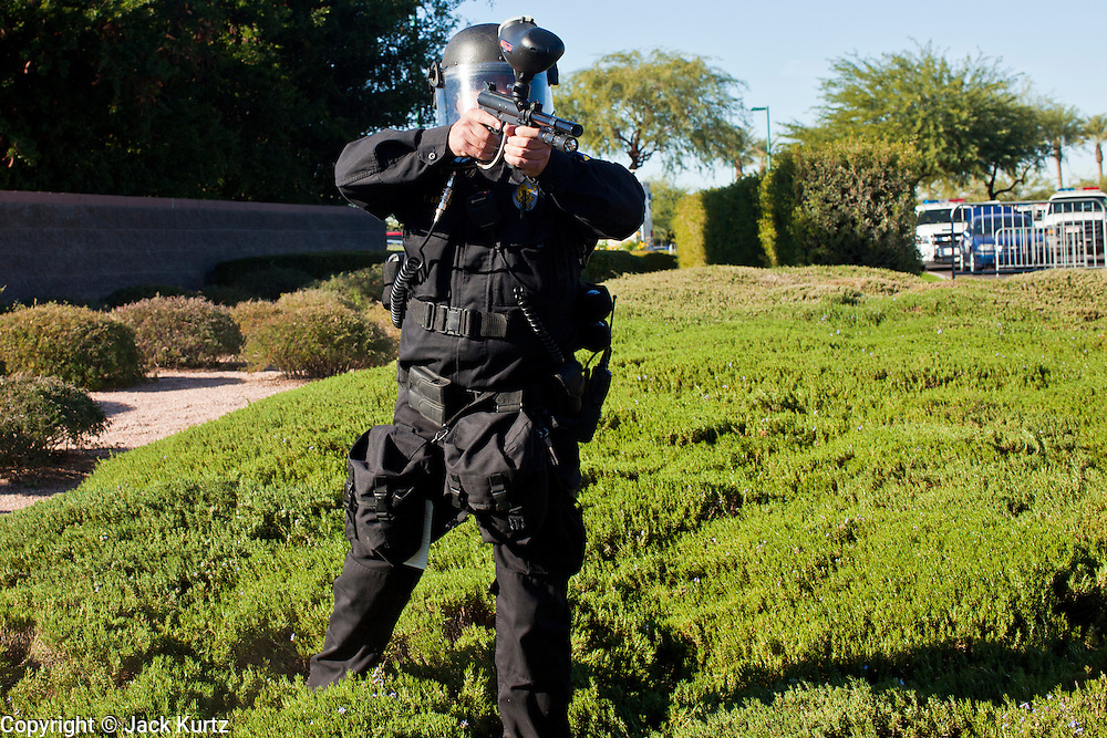 30 NOVEMBER 2011 - PHOENIX, AZ:    A Phoenix police officer aims his paint ball-pepper spray gun at anti-ALEC protesters in front of the Westin Kierland Resort and Spa. About 300 people picketed the American Legislative Exchange Council (ALEC) conference at the Westin Kierland Resort and Spa in Phoenix, AZ, Wednesday. The protesters claim ALEC, a conservative think tank, violates its tax exempt status by engaging in lobbying, a charge ALEC officials deny. Many conservative pieces of legislation, like Arizona's anti-immigration bill SB1070, originate with ALEC conferences (SB 1070 originated at an ALEC conference several years ago). Many of the protesters are also members of the Occupy movement.   PHOTO BY JACK KURTZ
