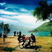 Picnickers watch from the shore as the TSS Earnslaw, the 100 year old vintage coal fired passenger steam ship sails on Lake Wakatipu, Queenstown, New Zealand. The popular tourist attraction is celebrating it's centenary year with celebrations planned for October 2012.  Queenstown, Central Otago, New Zealand. 29th February 2012. Photo Tim Clayton