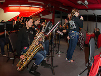 """Sabrina Desaulniers sings """"Santa Claus is Coming to Town"""" accompanied by the LHS Jazz Band during the spaghetti dinner prepares for guests at the Huot dining room on Tuesday evening.  (Karen Bobotas/for the Laconia Daily Sun)"""
