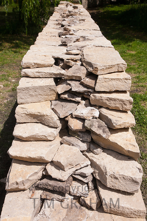 Newly built dry stone wall constructed of new Cotswolds stone using traditional old methods, UK