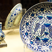 A bowl, plate, and jug featuring blue and white with turquoise Iznik glazed artwork from the period 1530-1545 in the Tiled Kiosk at the Istanbul Archaeology Museums. The Tiled Kiosk was commissioned by Sultan Mehmed II in 1472 and is one of the oldest buildings in Istanbul. It features Ottoman civil architecture, and was a part of the Topkapı Palace outer gardens. It was used as the Imperial Museum between 1875 and 1891 before the collection moved to the newly constructed main building. It was opened to public in 1953 as a museum of Turkish and Islamic art, and was later incorporated into the Istanbul Archaeology Museum. The Istanbul Archaeology Museums, housed in three buildings in what was originally the gardens of the Topkapi Palace in Istanbul, Turkey, holds over 1 million artifacts relating to Islamic art, historical archeology of the Middle East and Europe (as well as Turkey), and a building devoted to the ancient orient.