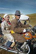 A Mongolian couple of their way to a festival on their motorcycle.<br /> Near Moron town, Khövsgöl province.