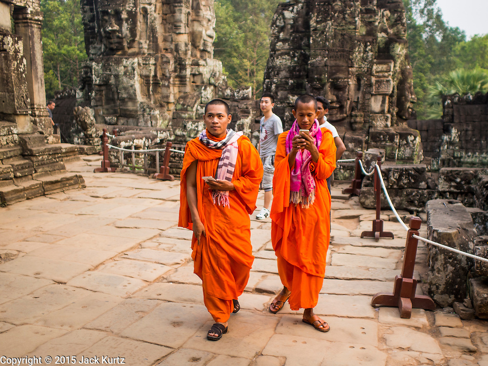 """14 MARCH 2105 - SIEM REAP, SIEM REAP, CAMBODIA: Buddhist monks walk around the Bayon, one of the temples in Angkor Thom, a part of the Angkor Wat complex. Bayon was built in 12th or 13th century CE. The area known as """"Angkor Wat"""" is a sprawling collection of archeological ruins and temples. The area was developed by ancient Khmer (Cambodian) Kings starting as early as 1150 CE and renovated and expanded around 1180CE by Jayavarman VII. Angkor Wat is now considered the seventh wonder of the world and is Cambodia's most important tourist attraction.  PHOTO BY JACK KURTZ"""