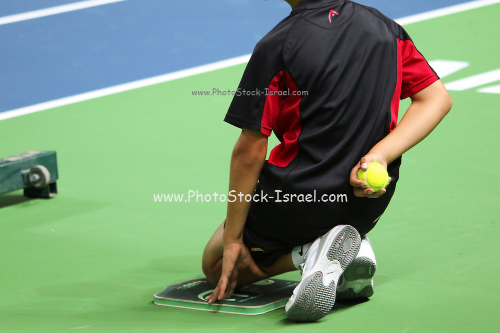 ballboy kneeling on the side of a tennis court
