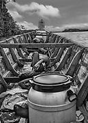 Transport fluvial, Maroni, 2015.<br /> <br /> Retour à Albina pour des ouvriers rentrant d'un chantier d'orpaillage clandestin. <br /> Lieu de vie et de passage, le Maroni reste la principale voie d'accès pour les communes isolées de l'Ouest guyanais. Une liaison aérienne régulière a été ouverte pour desservir les communes de Grand-Santi et Maripasoula en moins de deux heure de vol, elle ne concerne que le transport des personnes en situation régulière pouvant justifier d'une identité. Le fret et les personnes sans papier passent par le fleuve. Il faut compter deuxjours au départ de Saint-Laurent pour rejoindre Grand-Santi, trois pour Maripasoula.<br /> Les transporteurs réguliers guyanais ne prennent théoriquement plus les passagers. Pour des raisons évidentes de respect de la légalité française, Albina qui fait face à Saint-Laurent sur la rive surinamaise du Maroni concentre la majorité des activités de transport à destinations des chantiers aurifères guyanais illégaux et chaque matin les piroguiers surinamais d'Albina organisent des départs pour remonter le fleuve et alimenter les sites clandestins ou les communes isolées.