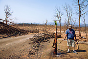 """08302018 - Redding, California, USA: Just weeks after a firenado destroyed everything he had Jose Brinones waters plants regrowing in the stark fire burned landscape. """"They want to live,"""" said Brinones who lost his house, workshop, his bees (Briones is a bee keeper), and vehicles burned during the fire tornado of the Carr wildfire, which destroyed more than 1000 homes.  Briones said he escaped with his family with only a couple minutes to spare, but lost everything else. (Photo by Jeremy Hogan)"""