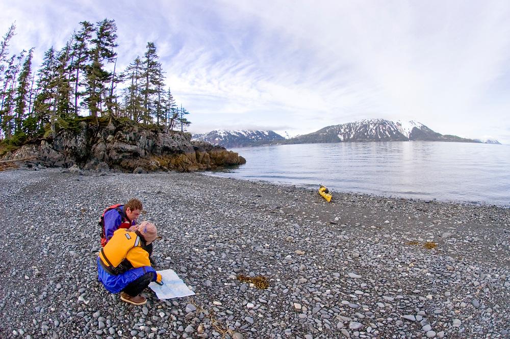Alaska. Decision Point State Marine Park. Kayakers Suzie Hanlan and Jason Lucas navigate their next destination on the beach of Decsion Pint at Passage Canal / Blackstone Bay.