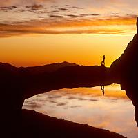 BACKPACKING, Hiker enjoys dawn over small lake near Mt.Whitney, John Muir Wilderness, Sierra Nevada, CA  (MR)