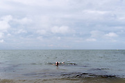 A wild swimmer swims back to shore in the tidal waters of the Thames Estuary, on 25th July 2021, in Whitstable, England.