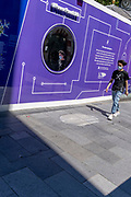 A man wearing a cross on his t-shirt walks past a mirror, part of a hoarding that screens off refurburshment works in the West End's Leicester Square, on 16th July 2021, in London, England.