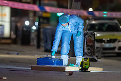 © Licensed to London News Pictures. 23/04/2021. London, UK. A forensic investigator gathers evidence on Barking Road in Canning Town following the fatal stabbing of a 14-year-old boy. Police were called at 15:56 BST on Friday, 23 April to reports of an assault in Barking Road, E16. Metropolitan Police officers attended with medics from the London Ambulance Service and the London Air Ambulance. They found a 14-year-old male who had been stabbed. He was pronounced dead shortly after 16:30 BST. Photo credit: Peter Manning/LNP