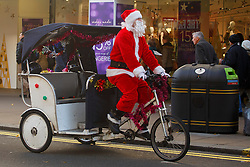 © licensed to London News Pictures. London, UK 08/12/2013. A man dressed as father christmas riding a bicycle rickshaw on Oxford Street in London on Sunday, 8 December 2013. Photo credit: Tolga Akmen/LNP